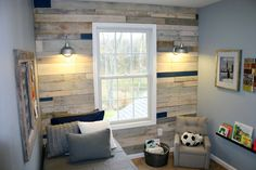 """We're with you if the term """"wood paneling"""" gives you flashbacks to The Brady Bunch rec room. But the owners of this house went in a totally different direction with that outdated standby, using rustic boards from (free!) shipping pallets and giving them a pretty whitewashed stain. Get the tutorial from East Coast Creative   - GoodHousekeeping.com"""