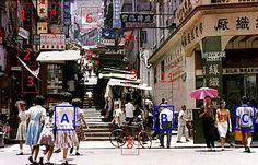 1970 --- 1 打橫放的牙醫陸貫如招牌仍在  2 只見布帳  3 小商店賣什麽呢?  4 又見某某酒家, 也見海鮮等字, 庸記在右邊, 藍色招牌  5 百瑞象牙變了明昌象牙, 舖位有個像書架的飾櫃  6 側側的中區差館仍可見  7 行人眾多  8 行人路太反光, 小缺口像在單車後輪下  9 斜階小商店密集  10 紅色的某某咖啡變了藍色, 下有新時代洋服, 打直有京都電髮廳, 前有美時珠寶… 和以前的美時玉石有關嗎?  11 兩格窗門和招牌仍在, 啟文仍在, 前方綠色鐵箱變了四四方方, 失去了小亭設計