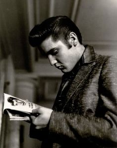 Elvis munches on a toothpick in the JeffersonHotel Coffee Shop near the magazine rack while he reads a story about Jerry Lewis, the comic.Richmond, VA June 30, 1956. Photo: Alfred Wertheimer