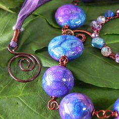 polymer clay beads of purple, blue and teal with silver leaf and alchohol ink in a spiral design by Polymer Princess, via Flickr