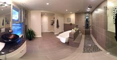 Panoramic image of bathroom including top mounted waterfall sinks and tub. Two sets of jets and three raindrop showerheads.