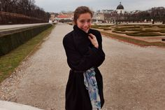 17.35 Miriam stein at the Belvedere Castle Vienna - wearing the A Day in a Life Navy Luxury Wool Coat with a Black Studded Leather Belt and the Blue Mountain Printed Silk Scarf