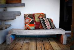 Banco de madeira (wooden bench with bright cushions)