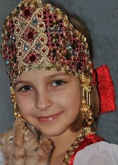 A girl has a kokoshnik on. It is the Russian traditional headdress.