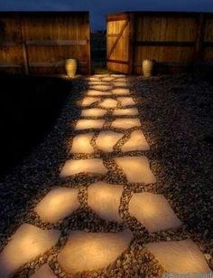 Rocks in a  pathway painted with glow in the dark outdoor paint. They soak up the sun and lead the way at night