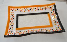 """Halloween black/orange wavy glass fused plate by YafitGlass. Pumpkins are such fun Halloween symbols!!! This plate has small pumpkins in both transparent and opalescent orange color. The center of the plate is black with orange stringers. Black frame and Halloween colors make this plate festive and big enough to hold your Halloween candies. Food safe, hand washing is recommended 12""""x8.5""""."""