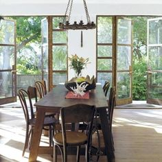 Love this dining room, generous french doors along wall, wood furniture with mix matched chairs, lots of lovely light, blonde wood floors