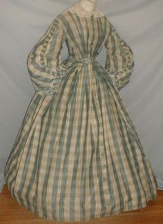 "1860s Slate Blue Plaid Dress | eBay fiddybee, silk & wool blend, pleated ruffles, decorative blue silk buttons on sleeves, attached white work muslin collar, bodice lined in cotton, front hook & loop closure, decorative blue silk buttons, skirt front trimmed with the buttons, skirt fully lined with cotton, light underarm discoloration to lining, small split on shoulder, tiny mend on other, couple of buttons fraying, bust: 32""; waist: 24""; skirt length: 39""; width at hem: 120"""