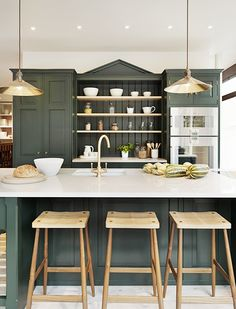 Gorgeous dark green kitchen cabinets accented with brass pendant lights, wood counter stools, a marble counter and a brass sink faucet. Dark Green Kitchen, Green Kitchen Cabinets, New Kitchen, Kitchen Interior, Kitchen Dining, Kitchen Decor, Dark Cabinets, Kitchen Ideas, Country Kitchen