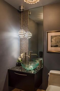Nancy Snyder's powder room design features a Lapia Silver granite vanity top, a to-the-ceiling wall of pearlized glass tile and mirror, a glass vessel sink and ultramodern lighting.