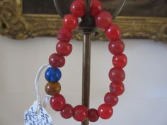 String of glass beads. Mostly red of varying colors, and blue and orange/yellow,