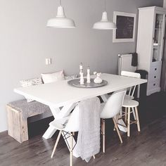 Soft greys in a minimalist Scandinavian style dining area. The faux sheepskin and knit throw really complete the look and add an inviting warmth.