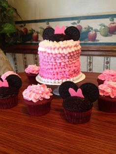 Minnie Mouse smash cake and cupcakes for a 1st bday party. Frost the cupcakes then cover frosting in Oreo crumbs by filing a bowl with crumbs and gently dunking the cupcake in the bowl until frosting is covered. The entire cookie is too much for the frosting to hold so separate the Oreo, pull out the cream filling and use each cookie as an ear. Bows were made out of Wilton melts. Ruffle cupcakes using the 104 tip and go back and forth instead of up and down…