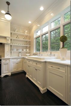 white kitchen with beautiful cabinets, open shelving and a wall of windows!