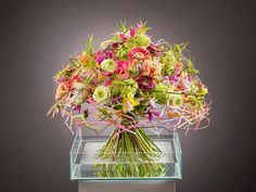 Leoni Gehr Vizemeisterin der Deutschen Meisterschaft der Floristen 2014 Mother's Finest  Fein abgestimmter Frühlingsstrauß in duftiger, fröhlicher Leichtigkeit. Seine Unbeschwertheit erhält dieses Bouquet durch die abgeknickten Strohhalme, die dekorativ in diesen ausgefallenen Blütenstrauß eingearbeitet sind. Sie setzen das frühlingshafte Farbenspiel fort und geben dem anmutigen Blütentanz Leichtigkeit.