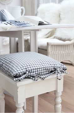 Simple, clean white furniture and blue gingham cushion ~ right up my alley!