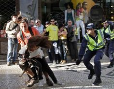 An officer readies to strike out at AFP photojournalist Patricia de Melo Moreira 23 Marzo 2012  Photograph: HUGO CORREIA/REUTERS