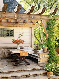 Similar to how banquette seating saves space in a small kitchen, a built-in bench is perfect for a small patio because it doesn't require extra space for chairs around the dining table. Here, the stone on the facade of the house continues around the perimeter of the patio for a fully integrated look.