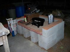 Outdoor concrete block cast iron cooking platform in my backyard off to the side of the patio -- red pavers on the 'deck' are covered with fire brick for extra heat protection. The block wall toppers are used to cover holes in the blocks and make handy shelf for spices & cooking tools. Nothing cemented, & has held up fine since May 2007, however the toppers do move when bumped. Makes cooking on the Lodge Sportsman's Grill & with my Dutch Ovens very easy. Saves my back, too.
