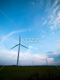 view of a wind farm at sunset. - View of a wind farm at sunset with sky in the background.