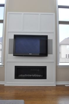 TV above Fireplace with In Wall Speakers. Fireplace framed by ...