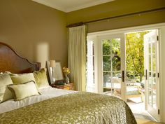 Designer Sarah Barnard relied on a green color palette for this traditional bedroom. Complementary bed linens, pillows and drapery are paired with the wall hue, while a pair of French doors open to reveal an outdoor patio. Bedroom Colour Palette, Bedroom Color Schemes, Bedroom Colors, Bedroom Decor, Bedroom Ideas, Bedroom Images, Paint Schemes, French Doors Bedroom, Colonial Bedroom