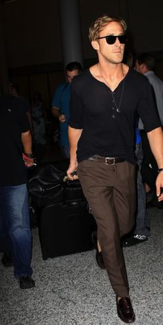 Ryan Gosling on the go: Brown slacks, low and loose black Henley, dress shoes, belt.