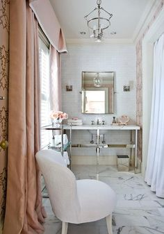 White master bathroom with blush pink accents features a pink wallpaper framing a window dressed in a blue pink valance complementing blush pink curtains hung behind a white chair and a mirrored nickel etagere placed adjacent to a nickel and marble 5-leg washstand positioned on white marble floors beneath a beveled vanity mirror flanked by nickel sconces mounted on white glazed linear backsplash tiles lit by a glass lantern.