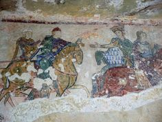 (Detail) 12th Century mural from Chapelle Sainte-Radegonde in Chinon, France. Duchess Eleanor of Aquitaine (Queen to King Henry II of England) seen here wearing a golden crown. Alongside is their daughter Joanna. Queen Eleanor is thought to be symbolically handing a falcon to her son and heir Duke Richard who would also succeed his father - King Henry II of England. The young man in the white hat may be Geoffrey Duke of Brittany - also one of Eleanor and Henry's sons.