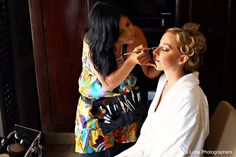 Sara working with Stephanie on last-minute makeup touches before her wedding at Playacar Palace