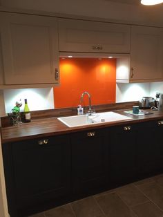 WOW 🖤💛 this kitchen was recently inspected after install for Mr and Mrs L in Chelmsford. It's striking with the splashes of orange in the fridge, glass and stools. The clients opted for two solid wood doors, to add flair to the design. They chose Neff appliances & laminate worktops. A gorgeous kitchen! #orangefridge #kitchendesign #cookaholics www.regalkitchens.co.uk