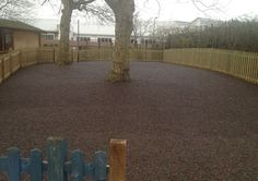 Red and green rubber mulch installed under trees makes a great play surface! Visit us for more playground ideas - www.billybounce.co.uk