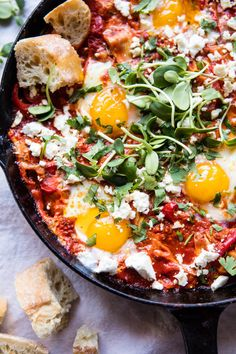 Artichoke Shakshuka - eggs slowly cooked in tomatoes, artichokes, & cheese, topped with fresh greens & served along side crusty bread. @halfbakedharvest.com