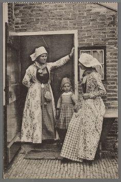 Twee vrouwen en een kind in de opening van een achterdeur. De vrouwen in wentke dragen het kostuum van de ongehuwde vrouw, herkenbaar aan de gevouwen zondoek en de rechts weggestoken halsdoek. Het meisje draagt het zgn. stavers hoofd, de kleding van meisjes tot het 16e jaar. De wentkes zijn niet origineel. 1905-1920 #Friesland #Hindeloopen