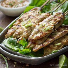 Grilované thajské kuřecí satay na bambusových špejlích na listy salátu na šedé talíř podávané s arašídovou omáčkou a limetkami.