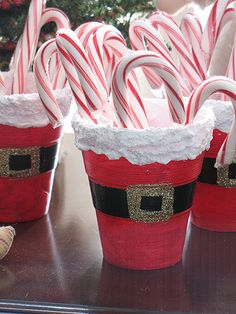 "Make these festive treat cups and fill them with candy canes, peppermint sticks, lollipops or plastic silverware for the ""child's"" table at Christmas dinner. Make smaller versions to hold hard Christmas candy by substituting small terra cotta pots instead of cups."