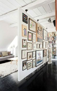 This space turned a room divider into a gallery wall. By filling the entire wall, the floating wall becomes both the backdrop and the focal point for the living room.