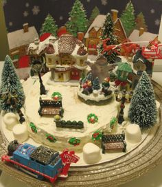Christmas Village Cake! with working lights and train! vanilla cake covered in fluffy white frosting with xmas props...marshmallows and candy sugar wreaths!