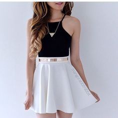 I love this look. Black crop top/tank, a white skater skirt, accessorized perfectly with a simple gold necklace and a matching belt.