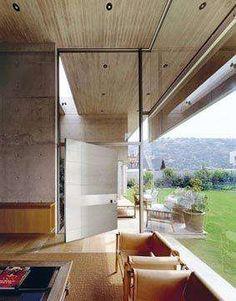 La porta a bilico verticale Synua di Oikos in vetro grigio
