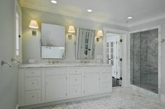 Glam master bathroom with marble basketweave tiles floor, seamless glass shower with marble subway tiles shower surround, white double bathroom vanity with marble countertop, rectangular pivot mirrors and light gray grasscloth wallpaper.