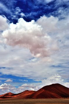 colors: blue sky, white clouds, and red rocky mountains