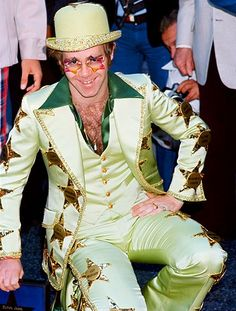 This is a color photo of Elton John receiving his Star on the walk of fame in Hollywood, California October Notice that his suit is a lime green but in another photo on this board, you will find that it is gold. I believe this photo may be more accurate.