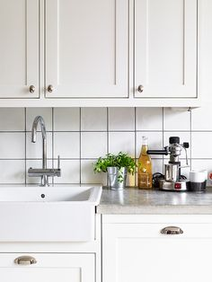 4 things: interior sink. cement countertop.  These cabinet handles. white back splash tile.