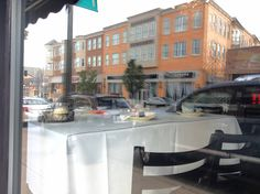 A table awaits customers at Salerno's Ristorante & Pizzeria in downtown Libertyville while businesses across Milwaukee Avenue are reflected in the front window.