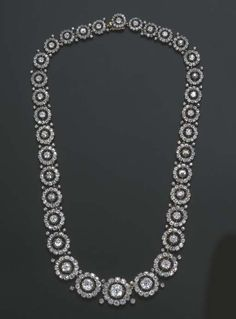 AN ATTRACTIVE EARLY 19TH CENTURY DIAMOND NECKLACE   Designed as a series of thirty-three graduated old-cut diamond clusters each with twin collet detail, mounted in silver and gold, circa 1830, 42.7 cm. long, in blue velvet fitted case