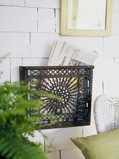 Made from an old metal heating grate. I like the idea of a magazine/paper rack out on the porch.