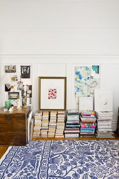 These books are just stacked neatly on the floor, with low-hung art on the walls (and a few perched onto the stacks).