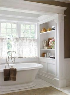 Bathroom with a view! Love the open shelving that looks like a bookcase and the free standing tub.