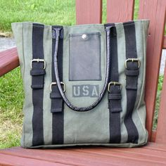 """The strapped tote has taken a traditional military knapsack look with upscale edgy appeal! The tote features black leather handles and 4 black straps with antiqued metal buckles on a green khaki canvas with print USA graphic and a leather snap pocket and a top with a magnetic closure.Signature Mona B cotton lining with an internal slip pocket, 4"""" x 4"""" and an internal triple slip pocket, measuring 9.75"""" x 5.75"""" for your phone, cards, or keys. Bag measures 14"""" W x 15"""" H x 3"""" D with 9"""" Handle…"""